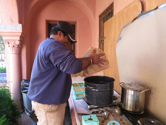 Raj gently placing the beeswax block into the large pot